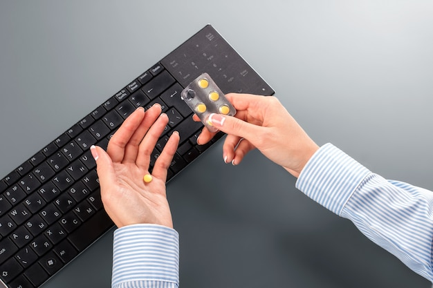 Frau nimmt pillen am arbeitsplatz. frau nimmt pille gegen kopfschmerzen. ich brauche eine kurze pause. dies sollte reichen.