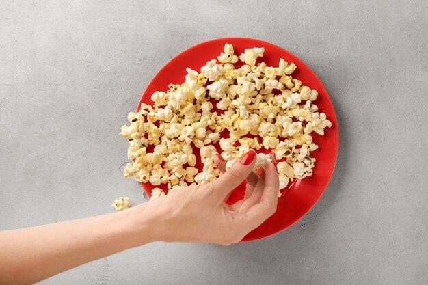 Frau nimmt popcorn vom teller auf dem tisch