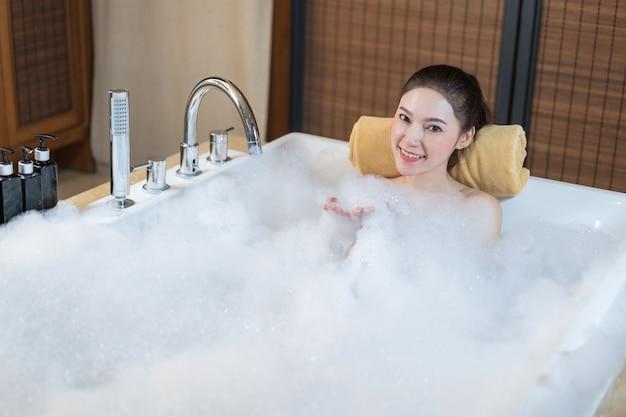 Frau nimmt schaumbad und spielt in der badewanne