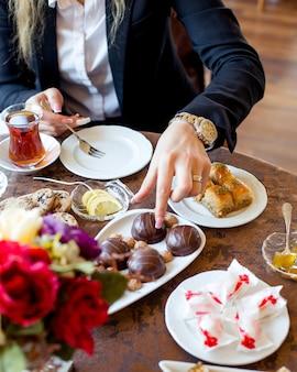 Frau nimmt schokoladenkuchen, um mit tee zu essen