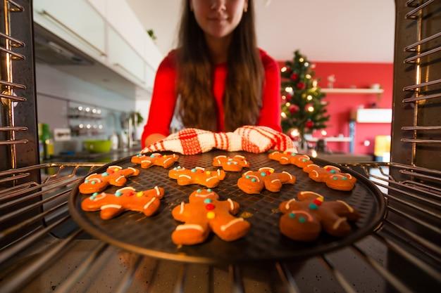 Frau nimmt vorgefertigte lebkuchenmänner aus dem ofen, der für weihnachten sich vorbereitet