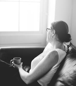 Frau nippt an einem getränk sitzt auf einem counch