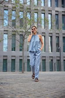 Frau nutzt roaming-verbindung für kommunikationsspaziergänge durch die stadt ruft den betreiber an, um den kontostand zu überprüfen, trägt blaues sommerkostüm und sandalen