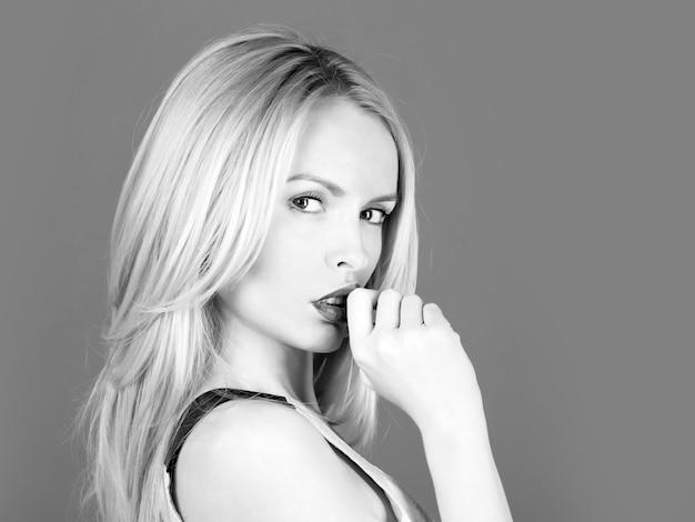 Frau oder süßes mädchen mit den fingern am sexy mund. stilvolles make-up auf jungem gesicht, haut und blondem langem haar, frisur. schönheitspflege, kopierraum.