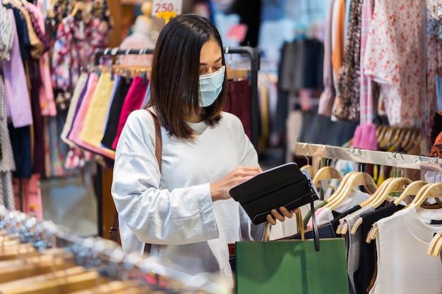 Frau öffnen geldbörse zur bezahlung für kleidung und tragen medizinische maske zur vorbeugung von coronavirus