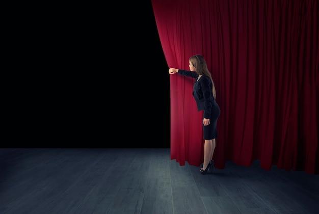 Frau öffnen rote vorhänge der theaterbühne
