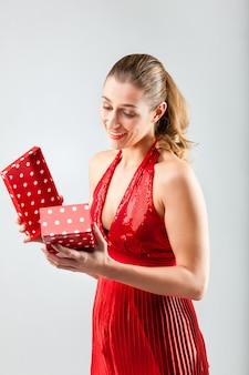 Frau öffnet das geschenk und ist glücklich