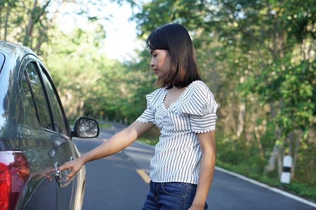 Frau öffnet die autotür.