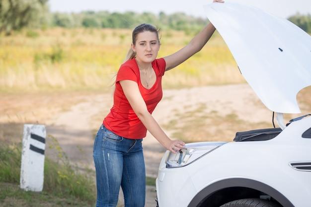 Frau öffnet die motorhaube des kaputten autos am straßenrand
