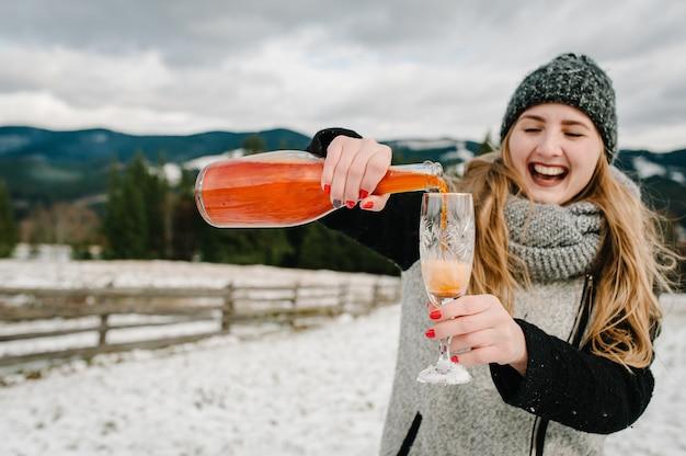 Frau öffnet eine flasche champagner und gießt in ein glas auf winterberge.