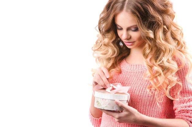 Frau öffnet eine geschenkbox isoliert auf weiß.