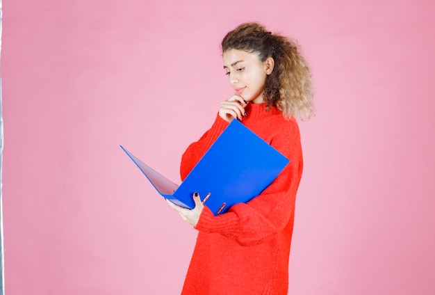 Frau öffnet einen blauen berichtsordner und sieht nachdenklich aus.