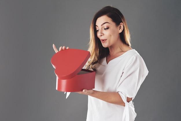 Frau öffnet rote herzförmige schachtel