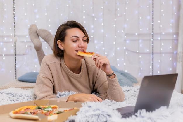 Frau ost fast food von der lieferung auf dem bett im schlafzimmer zu hause. frau allein, die fettes essen, pizza genießt