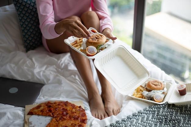 Frau ost fast food von der lieferung auf dem bett im schlafzimmer zu hause