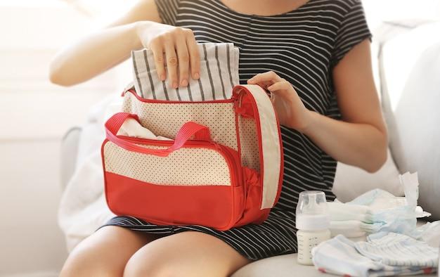 Frau packt ihre tasche mit kinderkram auf der couch