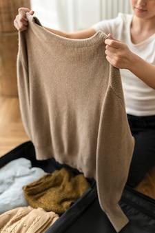 Frau packt ihre winterkleidung in ein reisegepäck