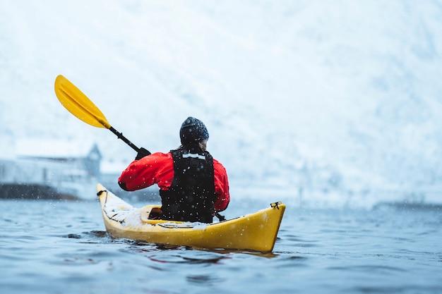 Frau paddelt ein kajak auf den lofoten, norwegen