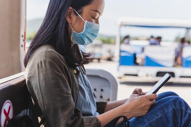 Frau passagier in der medizinischen maske unter verwendung des smartphones beim sitzen in flughafentransporten.