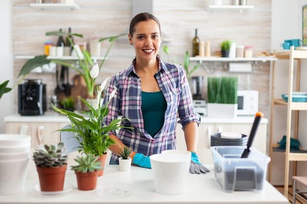Frau pflanzt dekorative blumen für zu hause mit fruchtbarer erde