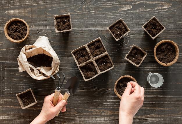Frau pflanzt setzlinge in den umweltfreundlichen töpfen