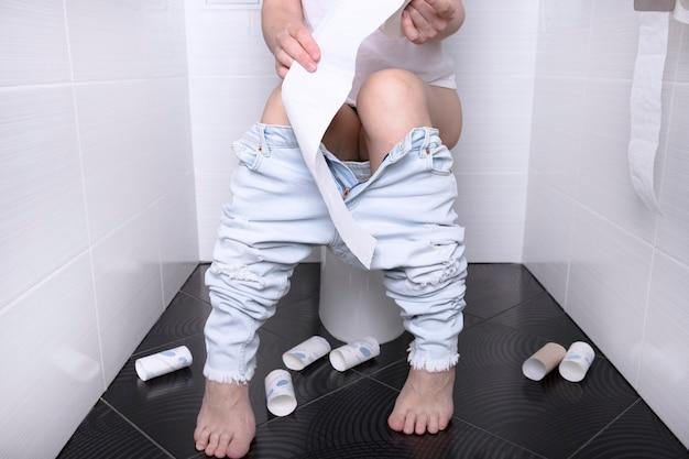 Frau pisst, mit durchfall auf einer weißen toilettenschüssel in der toilette mit einer papierrolle in der hand.