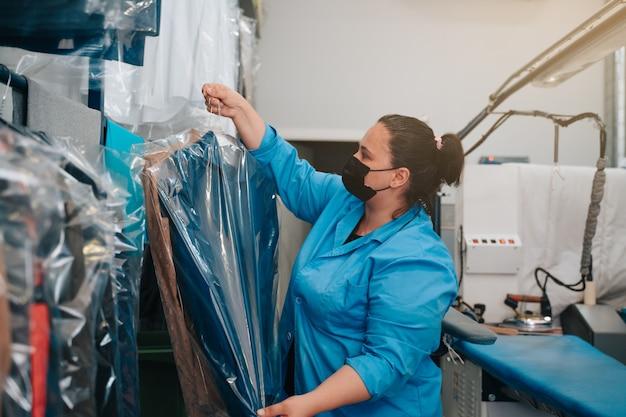 Frau platziert die anzugjacke, die sie in ihrem geschäft gebügelt hat