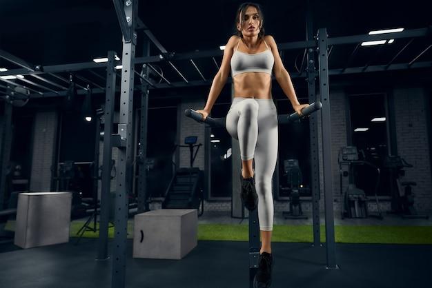 Frau posiert auf barren im fitnessstudio
