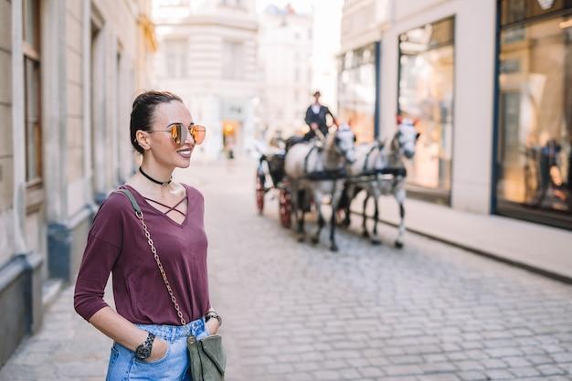 Frau posiert auf einer straße mit pferdekutsche