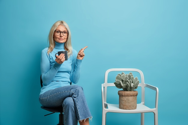 Frau posiert im büro auf einem bequemen stuhl zeigt auf eine leere stelle und hat eine kaffeepause