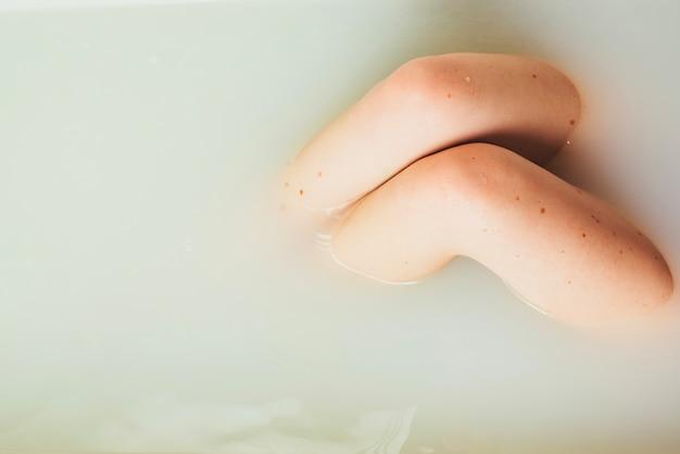Frau posiert im wasser der badewanne