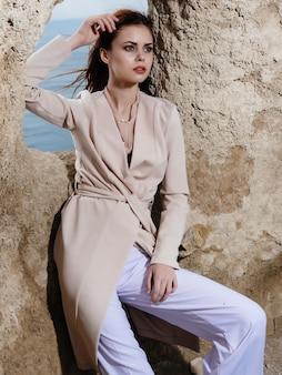 Frau posiert in der nähe von felsen im eleganten sandstil