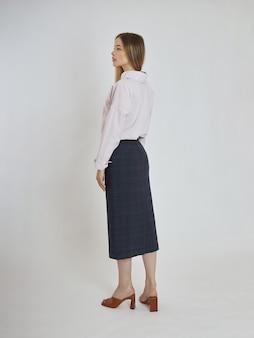 Frau posiert mit blauem rock und weißer bluse