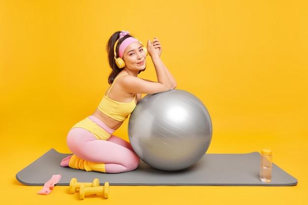 Frau posiert mit fitnessball auf matte trägt abgeschnittene top-leggings benutzt hanteln trinkt frisches wasser