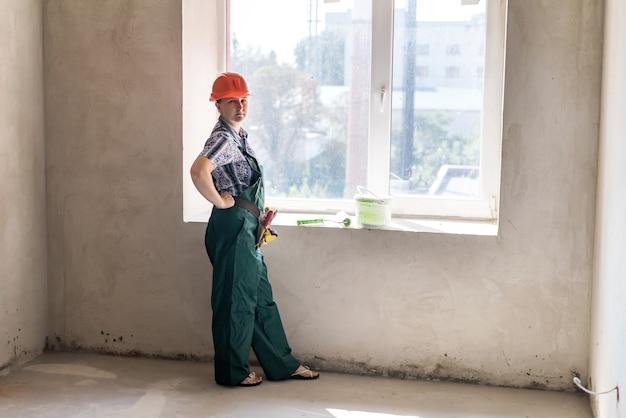 Frau posiert mit rolle zum malen und eimer farbe