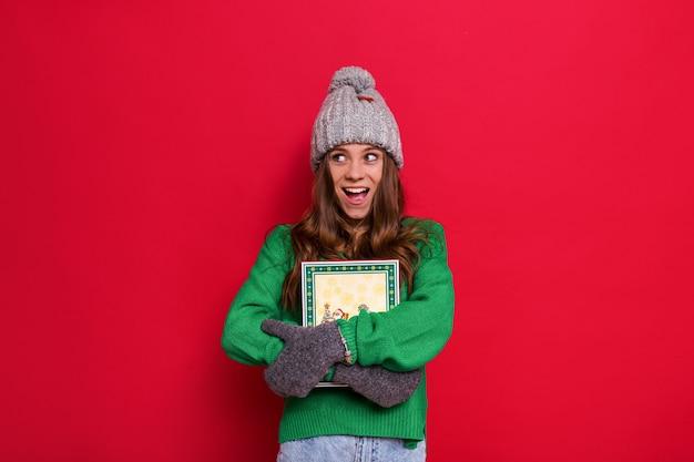 Frau posiert mit wintermütze und handschuhen, die ein weihnachtsgeschenk halten