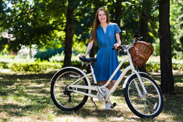 Frau posiert neben dem fahrrad
