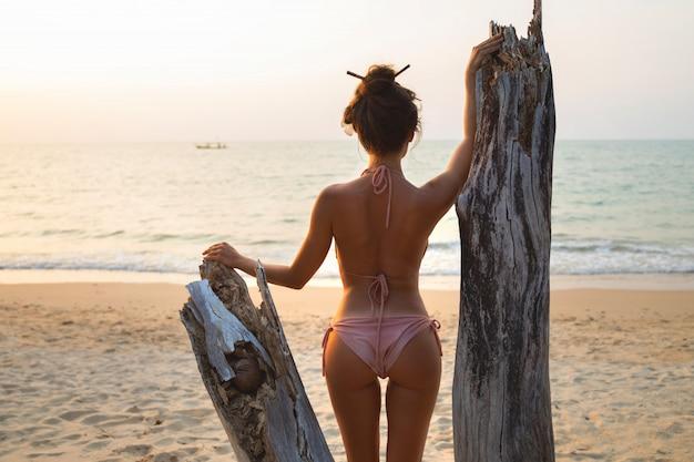 Frau posiert neben dem treibholz am strand bei sonnenuntergang
