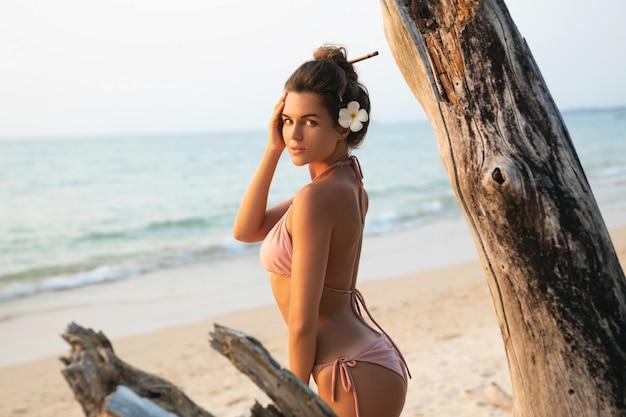 Frau posiert neben dem treibholz am strand