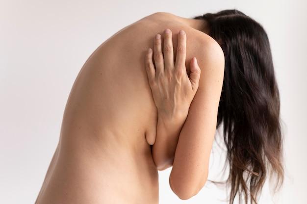 Frau posiert selbstbewusst nackt und zeigt sich zurück