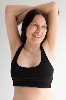 Frau posiert selbstbewusst und zeigt achselhöhle