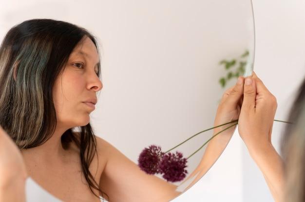 Frau posiert sinnlich mit einer blume