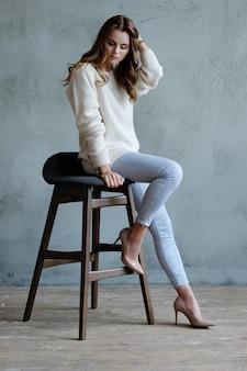 Frau posiert sitzend auf einem stuhl