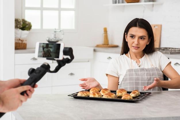 Frau präsentiert gebäck vor der kamera