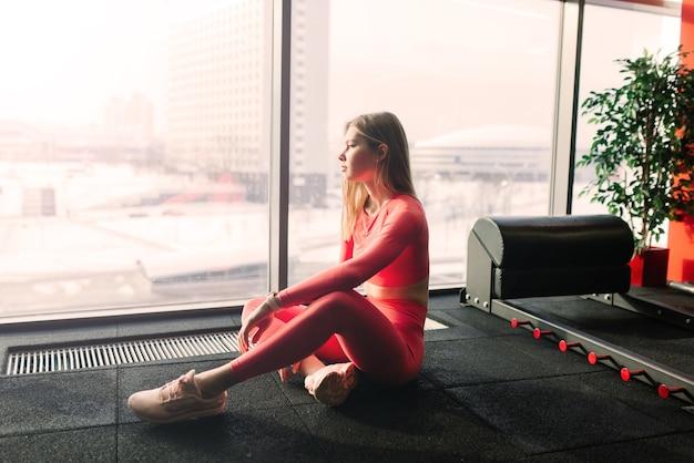 Frau praktiziert fortgeschrittenes yoga auf matte gegen ein großes fenster