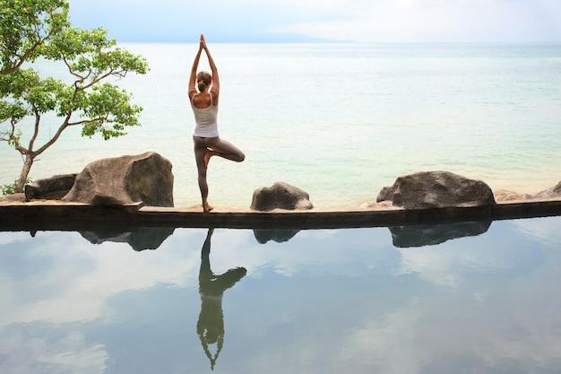 Frau praktiziert oder macht morgendliche meditation yoga in der natur am strand