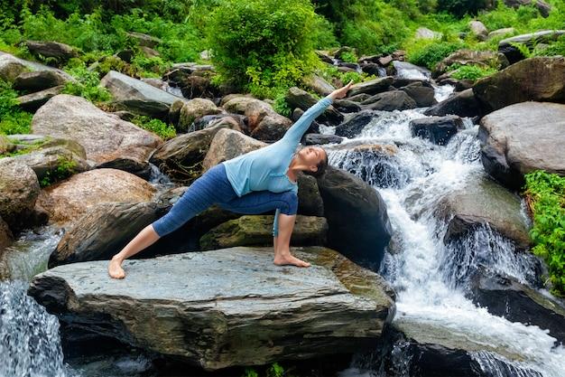 Frau praktiziert yoga asana utthita parsvakonasana im freien