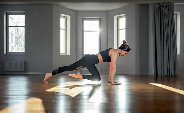 Frau praktiziert yoga in einem fitnessraum im morgengrauen. konzentration, schöner sonnenschein, dehnung, gesunder lebensstil.