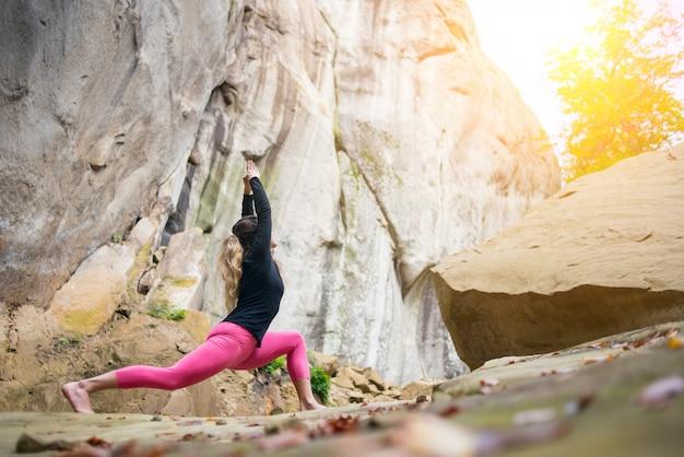 Frau praktiziert yoga und macht draußen asana