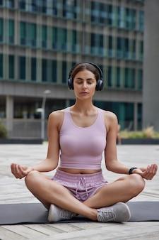 Frau praktiziert yoga und meditiert konzentriert beim sporttraining auf gedanken hört musik über kopfhörer erreicht erholung für psychische gesundheit posen auf fitnessmatte
